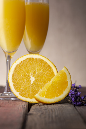 Mimosa cocktails in champagne glasses with orange juice and sparkling wine decorated with lavender leaves and orange slices Banque d'images