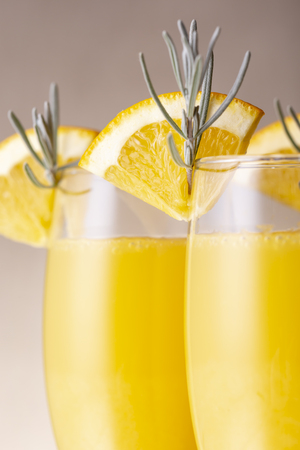 Detail of mimosa cocktails in champagne glasses with orange juice and sparkling wine decorated with lavender leaves and orange slices Banque d'images