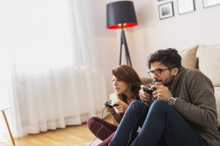 Couple in love enjoying their free time, sitting on the living room floor, playing video games and having fun