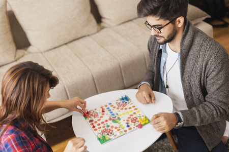 Couple in love sitting on the floor next to a table, playing ludo board game and enjoying their free time together. Woman repositioning her figurines and winning the game