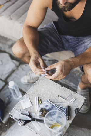 Detail of male hands unpacking a razor blade for cutting a heroin line Stock Photo