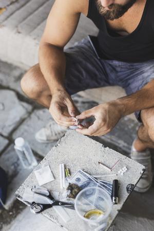 Detalle de manos masculinas desembalaje de una hoja de afeitar para cortar una línea de heroína Foto de archivo