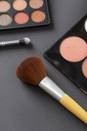 High angle view of an eyeshadow palette, highlighter palette, highlighter make up brush and an eyelid make up brush
