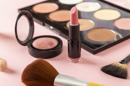 High angle view of various make up products on pink background. Make up brushes, blushes, face powders, highlighters, lip gloss and a lipstick