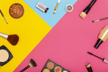 Flat lay of various make up products on colorful background with copy space. Make up brushes, blushes, face powders, corrector and highlighters