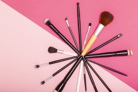 Flat lay of professional make up brushes set isolated on pink background 写真素材