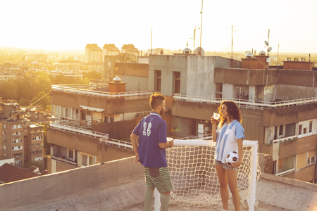 Young couple in love having fun on a building rooftop after playing football, drinking beer and enjoying a beautiful sunset over the city Banque d'images - 118131090