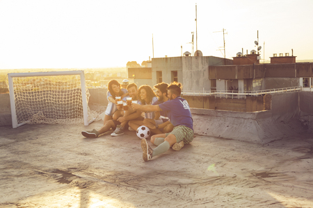 Group of young people sitting on a building rooftop, wearing jerseys, resting after a football match, drinking beer and making a toast Banque d'images - 118131091