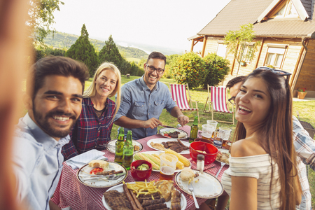 Group of friends having a backyard barbecue party, having fun taking selfies Banque d'images - 118131101