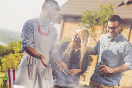 Group of friends having a backyard barbecue party, grilling meat, drinking beer and having fun on a sunny summer day Stock Photo