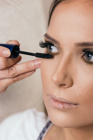 Make up artist working in a make up studio, putting mascara on female clients eyelashes