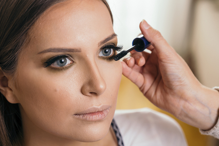 Make up artist working in a make up studio, putting mascara on female client's eyelashes Banque d'images - 118131174