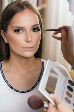 Make up artist working in a make up studio, shading the female client's eyelids Banque d'images - 118131176