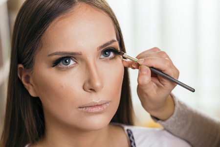 Make up artist working in a make up studio, shading the female client's eyelids Banque d'images - 118131189