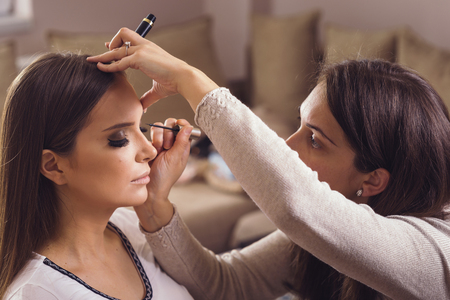 Make up artist working in a make up studio, putting eyeliner on female clients eyelids