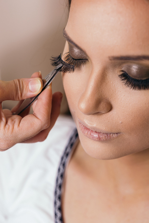 Make up artist working in a make up studio, putting artificial eyelashes on female clients eyelids with a tweezers