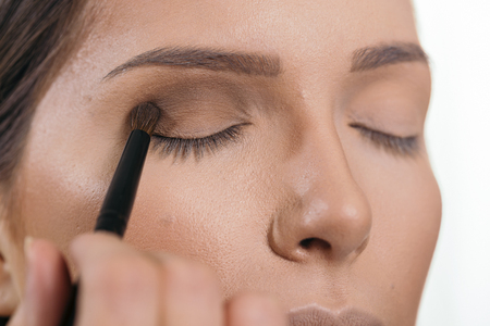 Make up artist working in a make up studio, shading the female client's eyelids Banque d'images - 118131220
