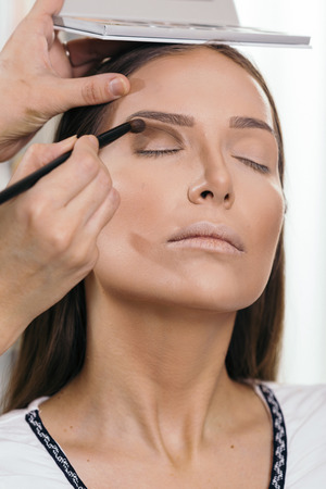 Make up artist working in a make up studio, shading the female client's eyelids Banque d'images - 118131221