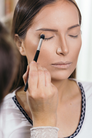 Make up artist working in a make up studio, shading the female client's eyelids Banque d'images - 118131228