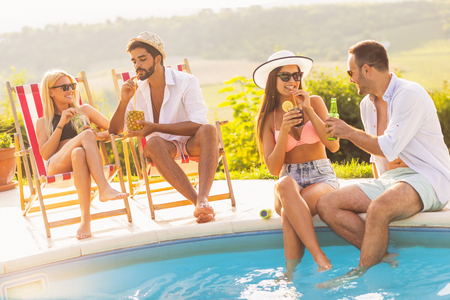 Group of friends at a poolside summer party, sitting at the edge of a swimming pool, drinking cocktails and beer and having fun