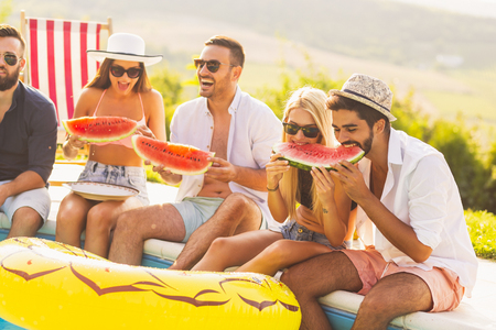 Group of friends at a poolside summer party, sitting at the edge of a swimming pool, eating cold watermelon slices and having fun