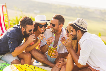 Group of friends at a poolside summer party, sitting at the edge of a swimming pool, drinking a pineapple cocktail and having fun Banque d'images - 118131342