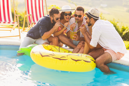 Group of friends at a poolside summer party, sitting at the edge of a swimming pool, drinking a pineapple cocktail and having fun Banque d'images - 118131343