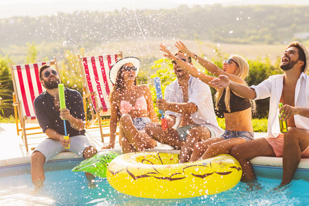 Group of friends at a poolside summer party, sitting at the edge of a swimming pool, drinking beer, splashing water and having fun