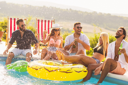 Group of friends at a poolside summer party, sitting at the edge of a swimming pool, drinking beer, splashing water and having fun. Focus on the guy on the right Stock Photo