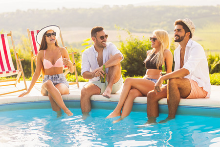 Group of friends at a poolside summer party, sitting at the edge of a swimming pool with legs in the water, drinking beer and having fun Banque d'images - 118131347