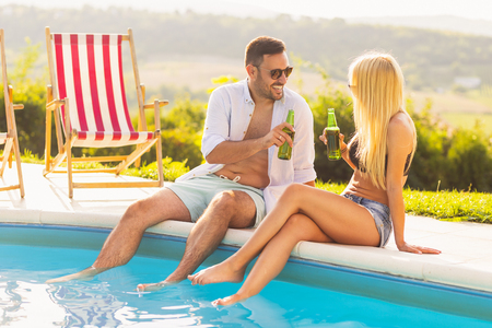 Couple in love at a poolside summer party, sitting at the edge of a swimming pool, drinking beer and having fun