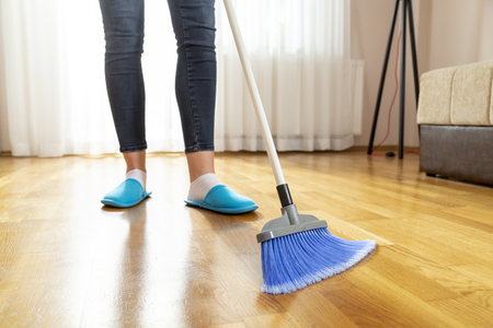 Detail of woman doing housework, holding a broom and sweeping floor