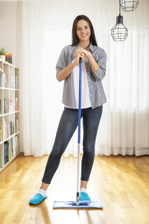 Woman holding a floor wiper and leaning on it, taking a break from doing housework Stock Photo