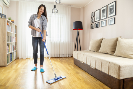 Woman holding a floor wiper and wiping floor, keeping the daily home hygiene and doing housework Stock Photo