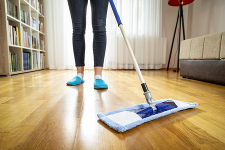Detail of a woman holding a floor wiper and wiping floor, keeping the daily home hygiene and doing housework