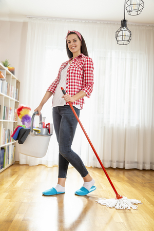 Woman holding a floor wiper and bucket filled with mops and cleaning supplies, doing house work and keeping the daily home hygiene Banque d'images - 118131367