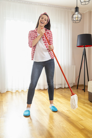 Woman holding a floor wiper and using it as a mike, singing and having fun while doing the housework