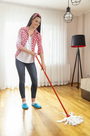 Woman holding a floor wiper and wiping floor, doing house work and keeping the daily home hygiene