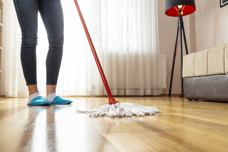 Detail of woman holding a floor wiper and wiping floor, doing house work and keeping the daily home hygiene