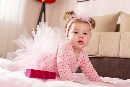 Beautiful little baby girl wearing pink tutu skirt, crawling on the floor, making her first independent moves Banque d'images - 118131397
