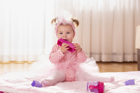 Beautiful little baby girl wearing pink tutu skirt, sitting on a duvet on the nursery floor, playing and chewing toy blocks