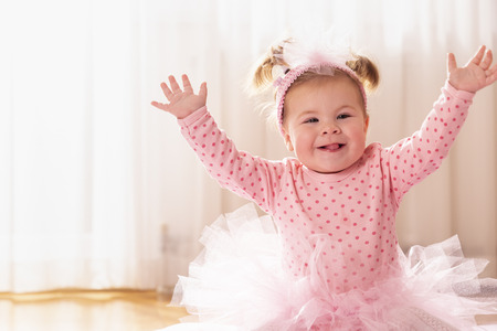 Beautiful little baby girl wearing pink tutu skirt, sitting on a duvet on the nursery floor, playing and smiling happily Stock Photo