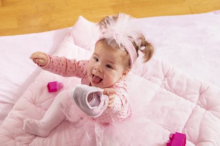 High angle view of baby girl wearing pink tutu skirt, sitting on a duvet and holding her shoe, playing Banque d'images - 118131418