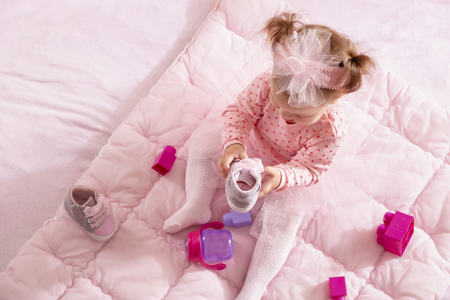 High angle view of baby girl wearing pink tutu skirt, sitting on a duvet and playing with her shoes and toy blocks Stock Photo