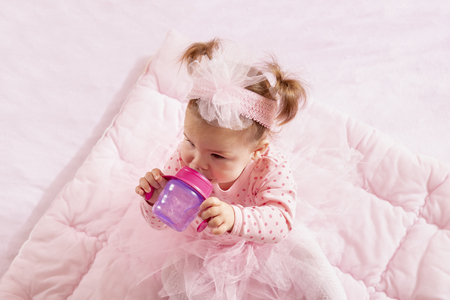 High angle view of a baby girl wearing pink tutu skirt, sitting on a pink duvet and drinking water from a bottle Banque d'images - 118131426