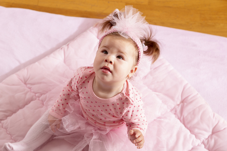 High angle view of a beautiful baby girl wearing pink tutu skirt sitting on a pink duvet, looking up and smiling Stock Photo