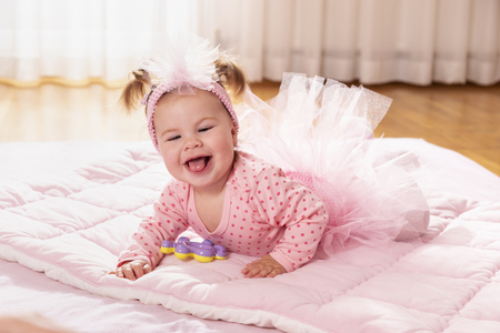 Beautiful little baby girl wearing pink tutu skirt, crawling on the floor, making her first independent moves Banque d'images - 118131433