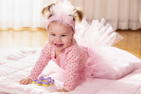 Beautiful little baby girl wearing pink tutu skirt, crawling on the floor, making her first independent moves