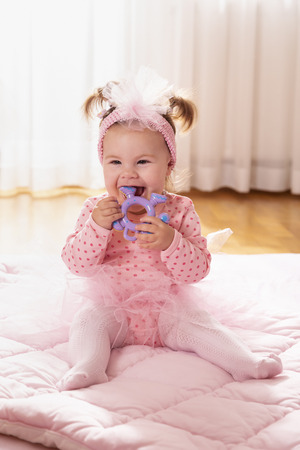 Beautiful little baby girl wearing pink tutu skirt, sitting on a duvet on the nursery floor, playing and chewing a rattle Banque d'images - 118131443