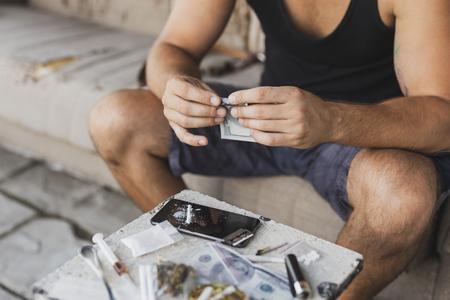 Adicto a las drogas enrollando un billete de un dólar por la inhalación de heroína desde la pantalla de un teléfono inteligente Foto de archivo